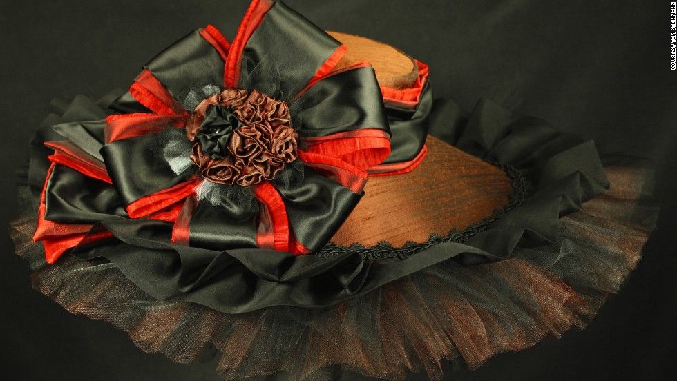 "To translate Wooden Phone's warm colors and ""diva personality"" in her design, Steinmann used dramatic layering of black and chocolate tulle around the brim. The looping and curling bow centerpiece is meant to reflect his ""watchful eye"" nature as well."