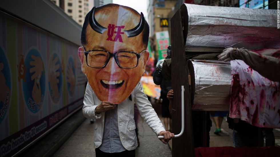 A protestor holds an oversized mask of billionaire tycoon Li Ka-shing, the chairman of Hutchison Whampoa, as hundreds of dock workers protest pay and working conditions in Hong Kong.