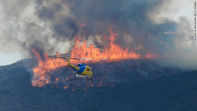 A Ventura County Fire Department helicopter in route to make a water drop on the wildfire in Pt. Mugu State Park on Friday May 3, in Newbury Park, California. Hundreds of firefighters continue to battle wind and dry conditions as the fires continue to burn.
