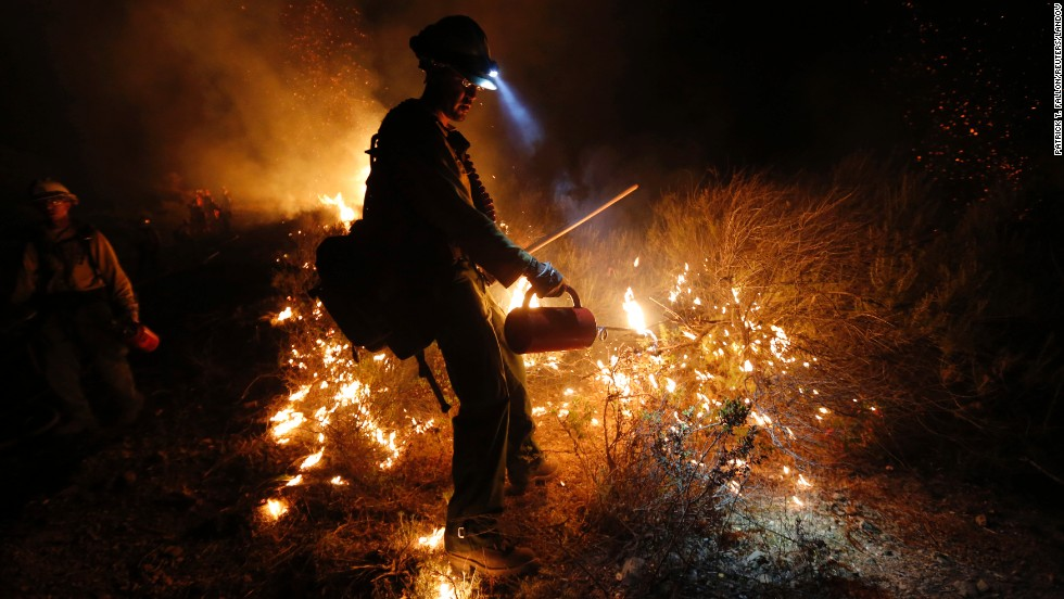 Firefighter Justin Romero of the New Mexico-based Silver City Hotshots uses a drip torch to build a backfire up the mountain off Potrero Road to control the Springs Fire near Newbury Park, California, on Friday, May 3. Winds have made fighting the Springs Fire blaze more difficult, and authorities have ordered mandatory evacuations of homes and the campus of California State University, Channel Islands.