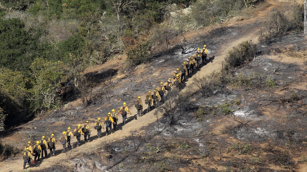 U.S. Forest Service Hotshot firefighters walk along the edge of the fire near Hidden Valley on May 4.