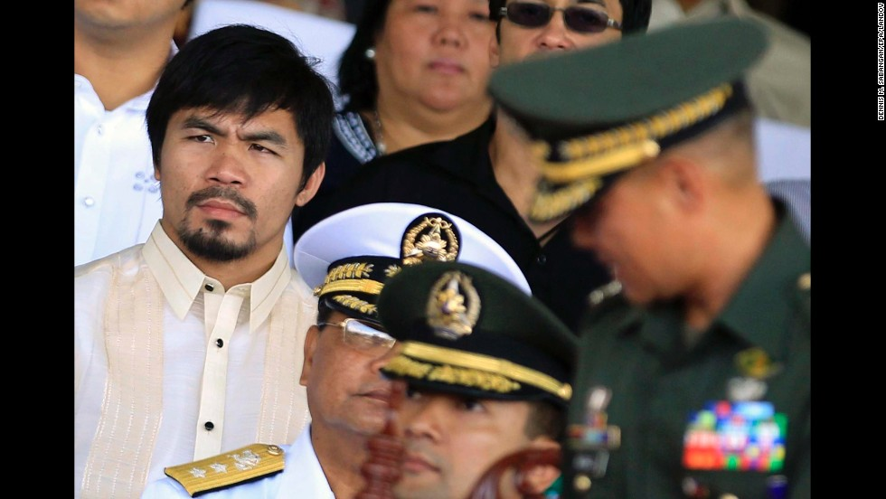 Pacquiao listens during the turnover ceremony for the new commanding general of the Philippine army at Fort Bonifacio on July 23, 2010.
