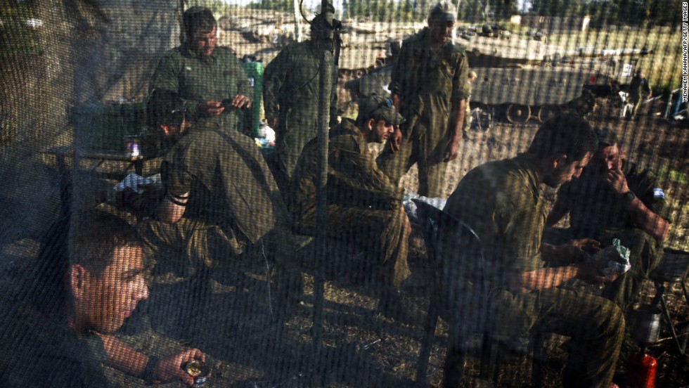 Israeli soldiers eat inside a net tent during a training break near the Syrian border on May 6.