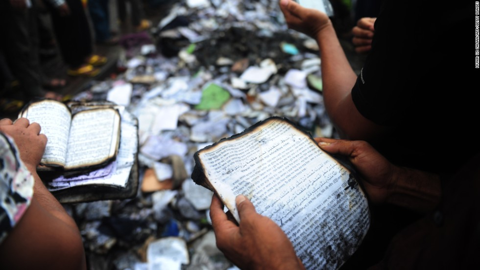 Bangladeshi people look at burned religious literature, including the Quran, near the national mosque Baitul Mukarram in Dhaka on May 6.