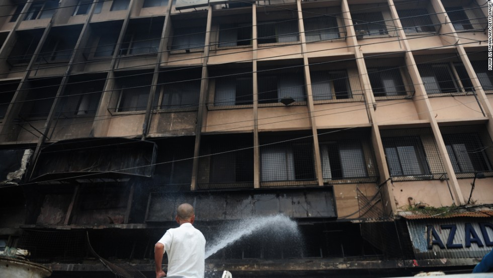 A Bangladeshi man extinguishes a blaze at a building near the national mosque Baitul Mukarram in Dhaka on May 6.