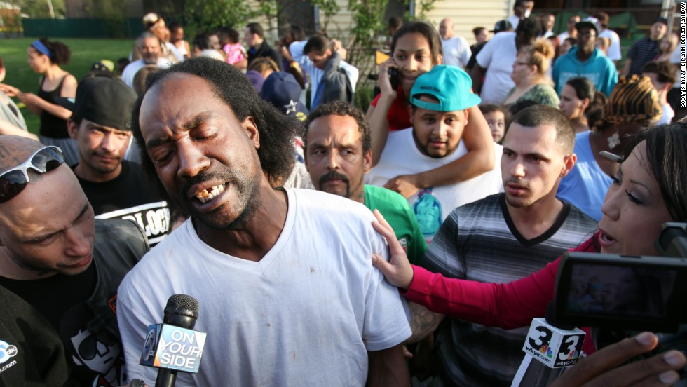Neighbor Charles Ramsey talks to media as people congratulate him on helping the kidnapped women escape on Monday, May 6. He helped knock down the door after he heard screaming inside.