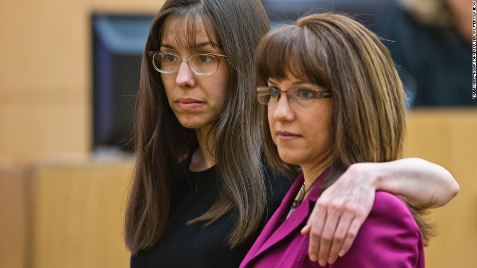 Arias puts her arm around defense attorney Jennifer Willmott after being asked to demonstrate how she had her arm around her sister in a photograph that had been admitted into evidence on March 4.