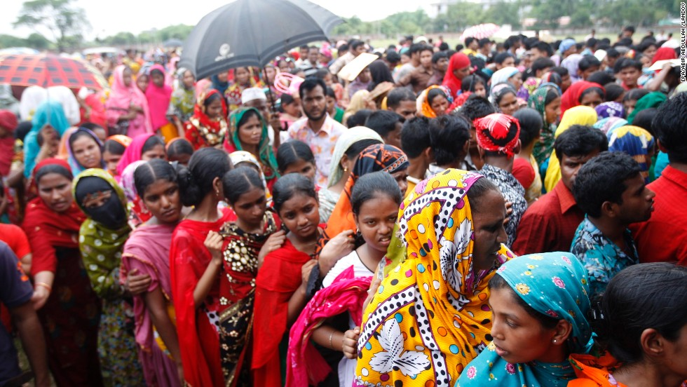 Garment workers who survived the building collapse line up to collect their salaries in Savar on May 8.