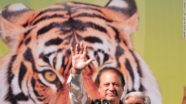 Former Pakistani Prime Minister Nawaz Sharif (C) waves as he addresses his supporters during an election campaign meeting in Islamabad on May 5, 2013. A roadside bomb exploded at an election rally in southwest Pakistan on May 5 killing two people, officials said as violence continued ahead of historic polls on Saturday. Campaigning has been marred by Taliban threats and attacks, which have killed 69 people since April 11, according to an AFP tally. Pakistan will elect its new government for the next five years in polls on May 11. The election of the national and four provincial assemblies will mark the first time a civilian government has completed a full term and handed over to another, in a country that has been ruled by the military for half its existence. AFP PHOTO / AAMIR QURESHI