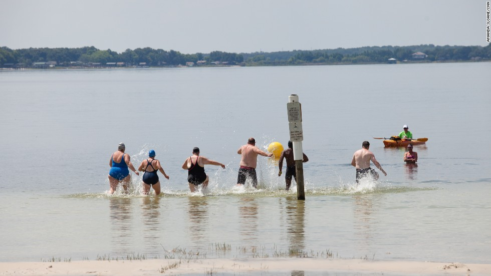 "Members of the ""6-Pack"" practice racing into the water before their first ocean swim."