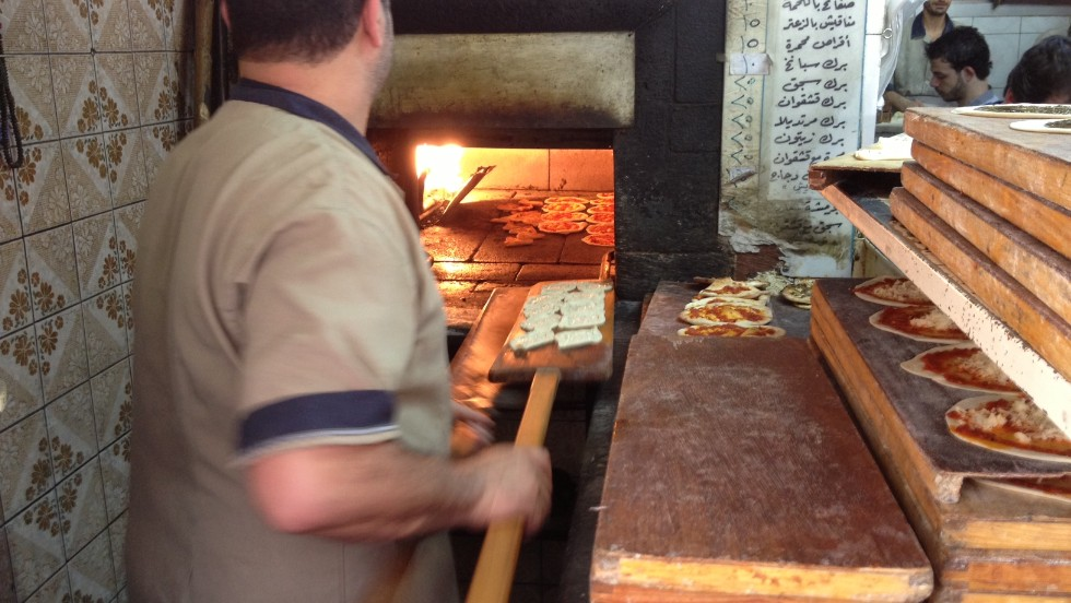 A baker makes zatar, a pastry akin to a mini-pizza with spices on top. Small bakeries offering cheap, tasty food are abundant in Damascus, and are usually full. However since the war began prices in the souk have soared and many goods are in short supply.