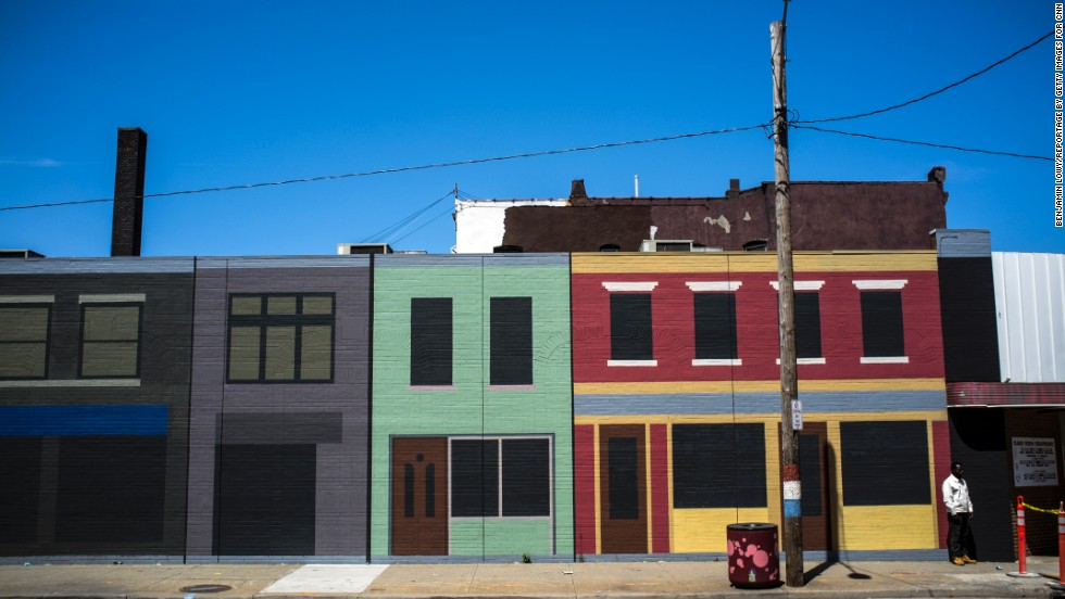 A man stands on Clark Avenue in front of painted buildings.