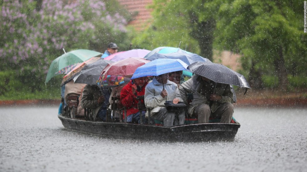 People take shelter under umbrellas during a boat ride in heavy rain on the Spreewald Canals near Luebbenau, Germany, on Sunday, May 12.