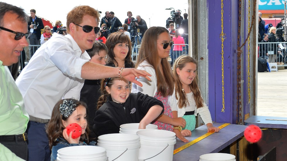 Prince Harry tries his hand at a stall with New Jersey Gov. Chris Christie during his visit to Mantoloking, one of the areas affected by Superstorm Sandy, on May 14, in Ocean Heights, New Jersey.