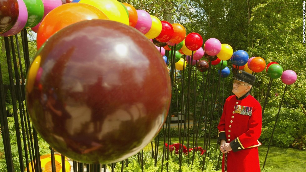"A Chelsea Pensioner inspects a 2004 work by Diarmuid Gavin called ""A Colourful Suburban Eden""."