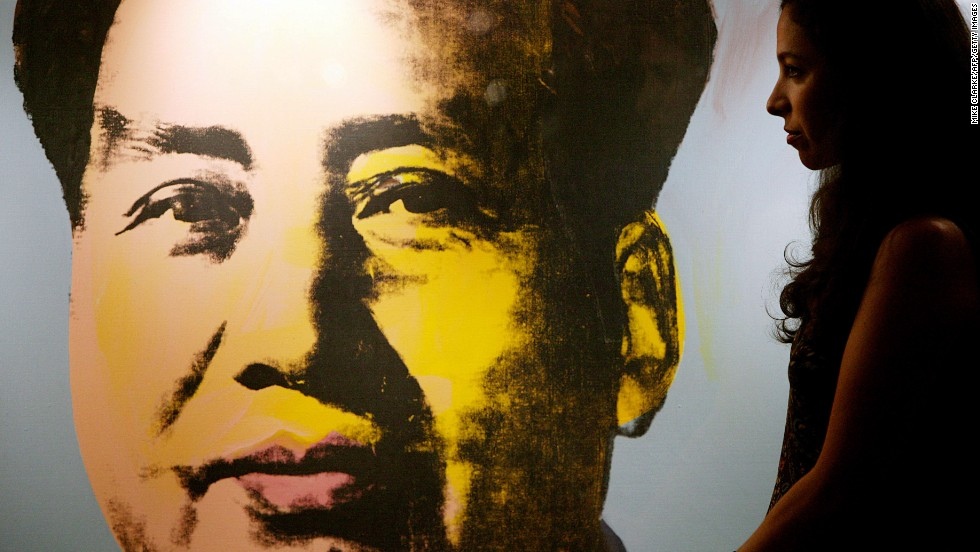 A Christie's art expert walks by a Mao portrait by Andy Warhol at a press preview in Hong Kong in October 2006.  The piece was auctioned to Hong Kong property tycoon Joseph Lau for US$ 17.4 million the  following month in New York, setting a world auction record for the artists.