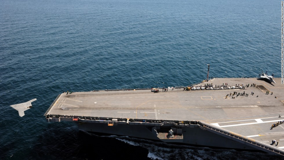 The drone launches from the flight deck of the aircraft carrier.