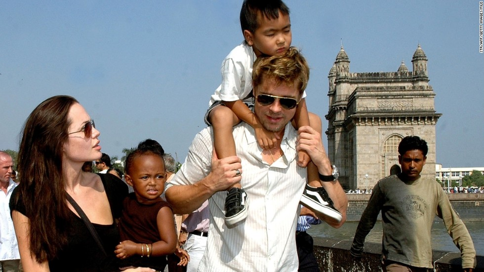 Here the proud mother holds daughter Zahara as partner Brad Pitt carries son Maddox during a stroll on the seafront promenade at the historic Gateway of India outside their hotel in Mumbai on November 12, 2006.