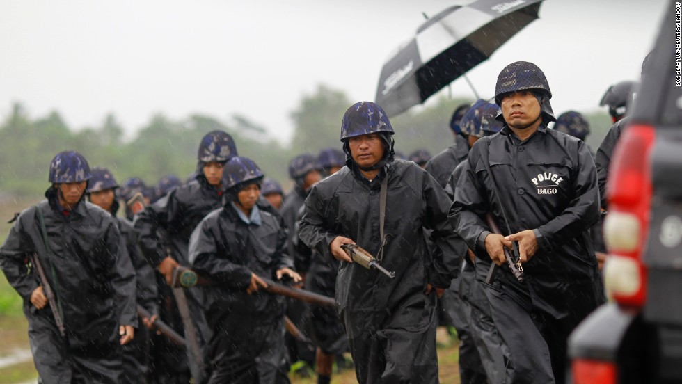 Police officers walk in the rain as they guard a Rohingya displacement camp outside Sittwe on May 14. Efforts to relocate some of the displaced appeared to be hindered by distrust of the security forces involved.