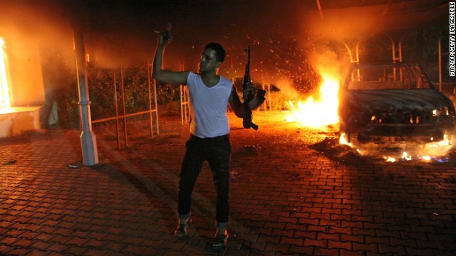 An armed man waves his rifle as buildings and cars are engulfed in flames after being set on fire inside the US consulate compound in Benghazi late on September 11, 2012. An armed mob protesting over a film they said offended Islam, attacked the US consulate in Benghazi and set fire to the building, killing one American, witnesses and officials said. AFP PHOTO (Photo credit should read STR/AFP/GettyImages)   Editorial image #: 	151807080