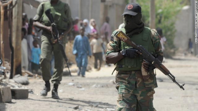 Soldiers walk on April 30, 2013 in the street in the remote northeast town of Baga, Borno State.