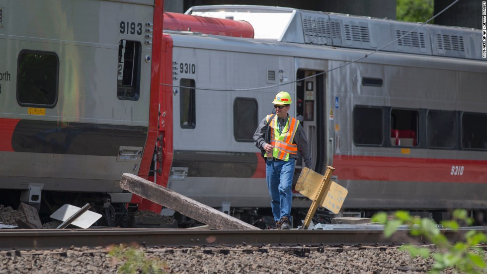 A Connecticut state investigator examines the scene of a Metro-North train collision on Saturday, May 18, in Fairfield, Connecticut. Two commuter trains collided during rush hour on Friday, sending dozens to the hospitals and shutting down a busy section of track, which is expected to affect commuters for weeks to come.