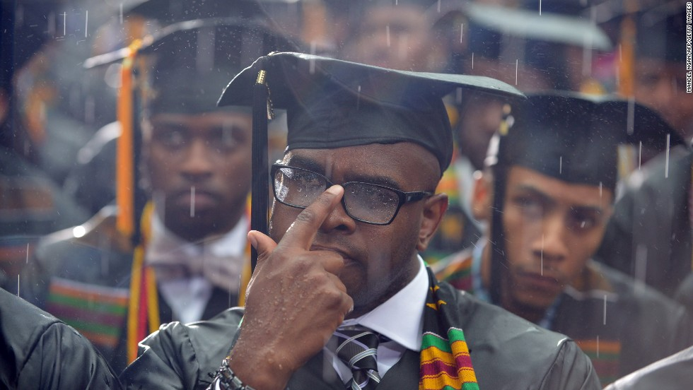 Graduating students listen to Obama as the rain warps their mortarboards.