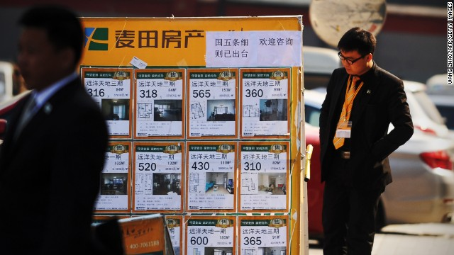 A real estate agent checks a property advertising board in Beijing on April 1,2013. Chinese home prices picked up in March as buyers rushed to beat new government policies aimed at cracking down on speculation, an independent survey showed on April 1. AFP PHOTO / WANG ZHAO (Photo credit should read WANG ZHAO/AFP/Getty Images)