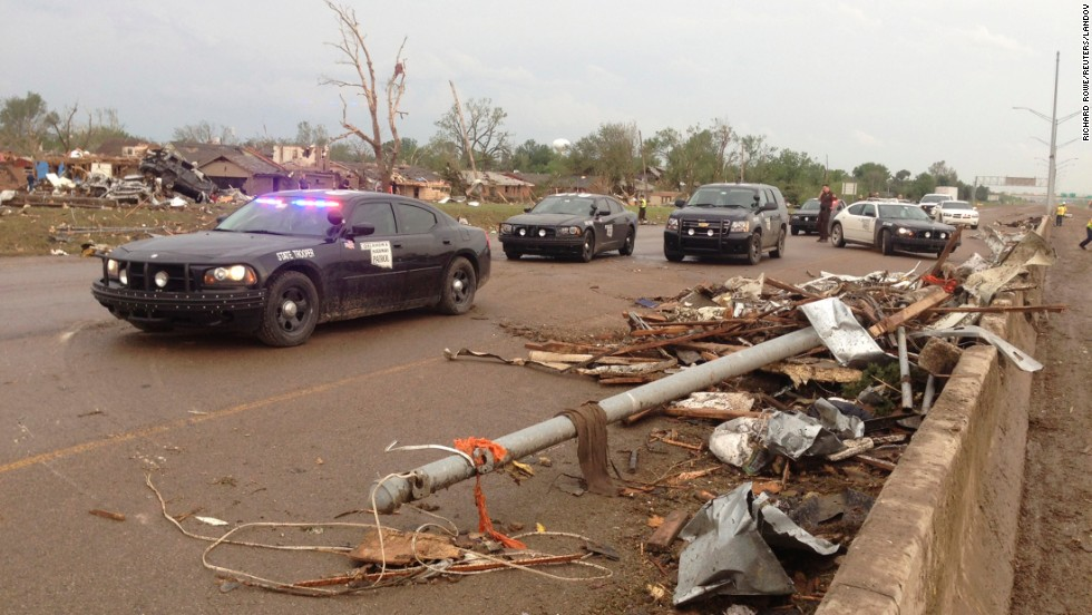 Law enforcement officers block a roadway in Moore where there was extensive damage from the tornado.