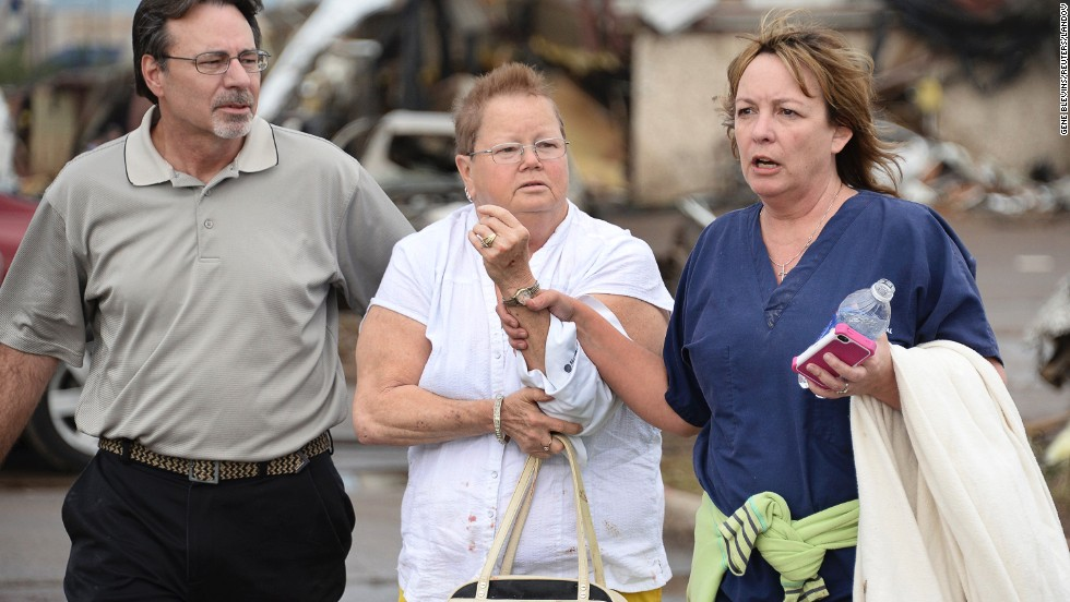 A woman with an arm injury is helped on May 20 in Moore.