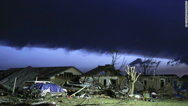 As dawn breaks, storm clouds roll in over a destroyed neighborhood on Tuesday, May 21, the day after a tornado hit Moore, Oklahoma.