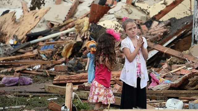 Two girls stand in rubble in Moore, Oklahoma. Melissa Brymer says parents can help kids by being honest and listening.