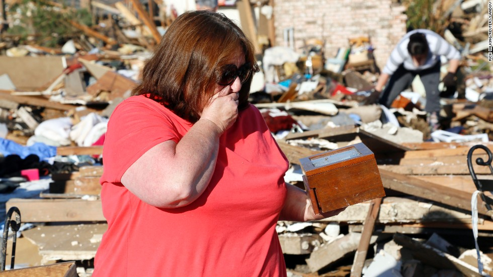 Kelli Kannady weeps after finding a box of photographs of her late husband in the rubble near where her home once stood in Moore on May 21.