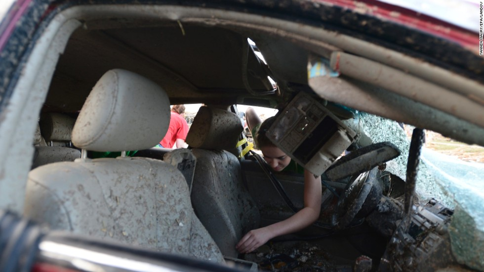 Natalie Johnson searches through her mother's destroyed car outside Briarwood Elementary School in Moore on May 21.