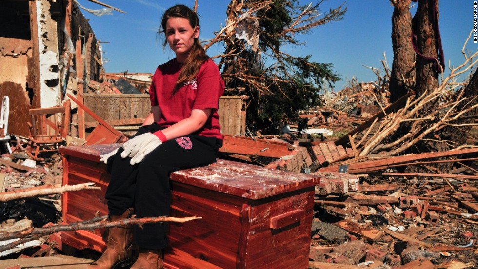 Payton Jo Lindsey sits on her grandmother's hope chest amid the ruins where her family's home once stood.