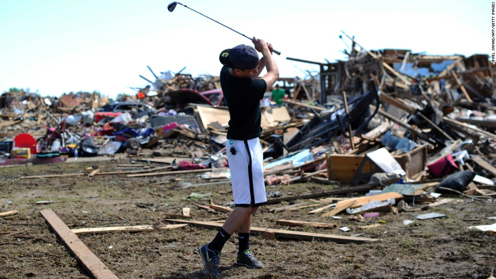 Michael Pritz swings a golf club while taking a break from helping his friend to salvage belongings on May 22.