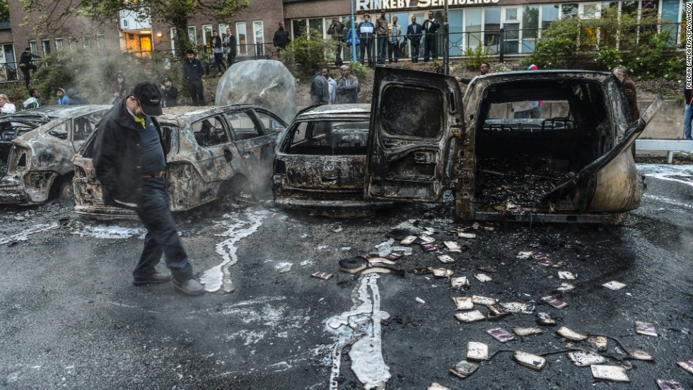 A man examines the debris around a row of burnt cars in the Stockholm suburb of Rinkeby on Thursday, May 23.
