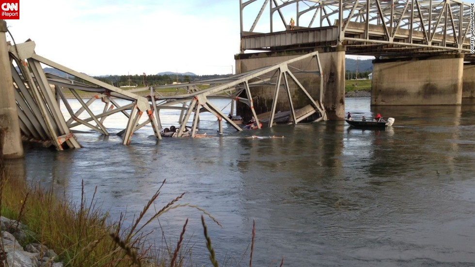 People examine the collapsed section of the bridge in this photo shot by iReporter Adrian Adrande.