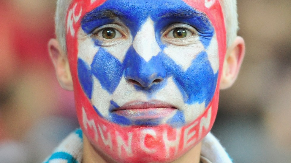 A fan of Bayern Munich wears face paint in support of his team during the match.