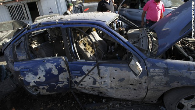 Lebanese men inspect destroyed cars after two rockets exploded in Shiah, a southern suburb of Beirut, on Sunday.