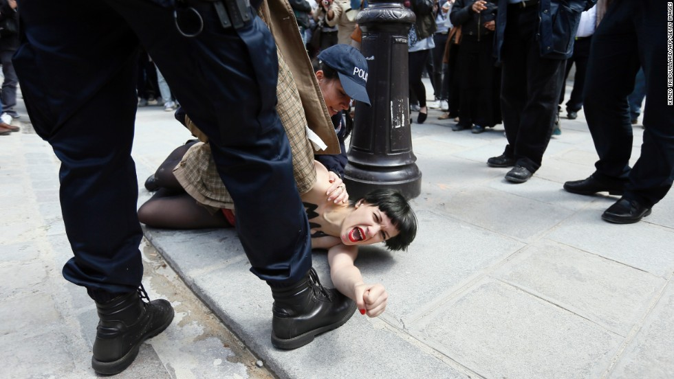 "A member of the FEMEN feminist activist group with writing on her chest reading ""May fascists rest in hell"" is arrested by police officers after taking part in a protest at Notre Dame Cathedral in Paris on Wednesday, May 22.  The protesters were demonstrating against the suicide of a far-right activist inside the cathedral the previous day."