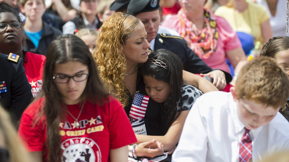 "Crowds listen as Obama honors U.S. military service members on Memorial Day. He called Arlington National Cemetery ""a monument to a common thread in the American character."""