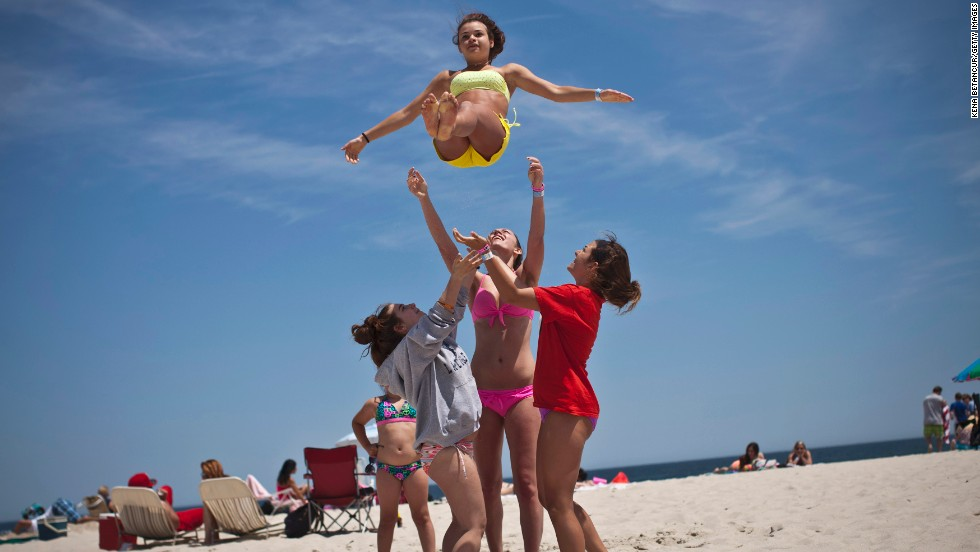 Emilie Sullivan is thrown into the air by her friends as they play on the beach in Seaside Heights.