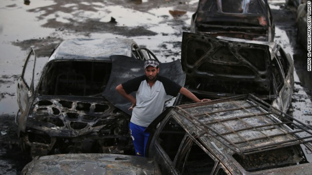 Iraqi men gather at the scene of one of the two car bombs that exploded in Baghdad's Habibiyah area on May 27, 2013. Attacks in the Baghdad area and northern Iraq killed 58 people, the latest in a wave of