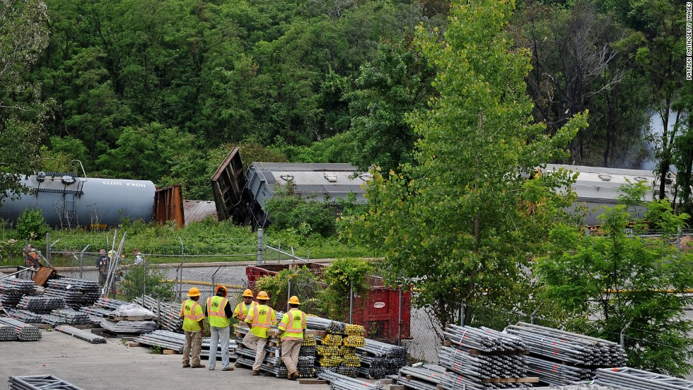 Workers gather around as damaged train cars from the derailment lie strewn along the tracks.