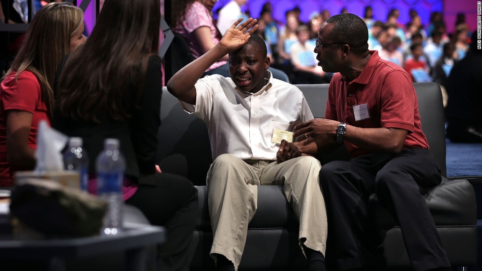 "Eboseremhen Eigbe of Galloway, New Jersey, is comforted by his father after he misspelling the word ""meiosis"" during the third round on May 29. Meiosis is the complex nuclear process that results in the production of cells (as gametes) with half the number of chromosomes of the original cell."