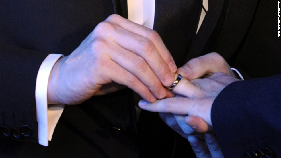 a same sex couple exchange wedding rings at their marriage ceremony - Same Sex Wedding Rings