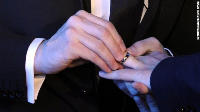 a same sex couple exchange wedding rings at their marriage ceremony - Gay Wedding Ring