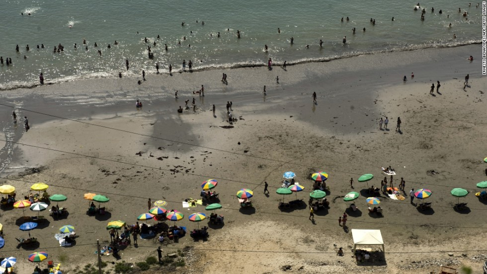 People enjoy a day at the beach of La Costa Verde Bay in Lima.