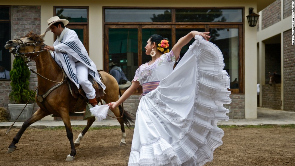 A man rides a Peruvian Paso horse next to a woman performing the traditional marinera dance in Lima on February 7.